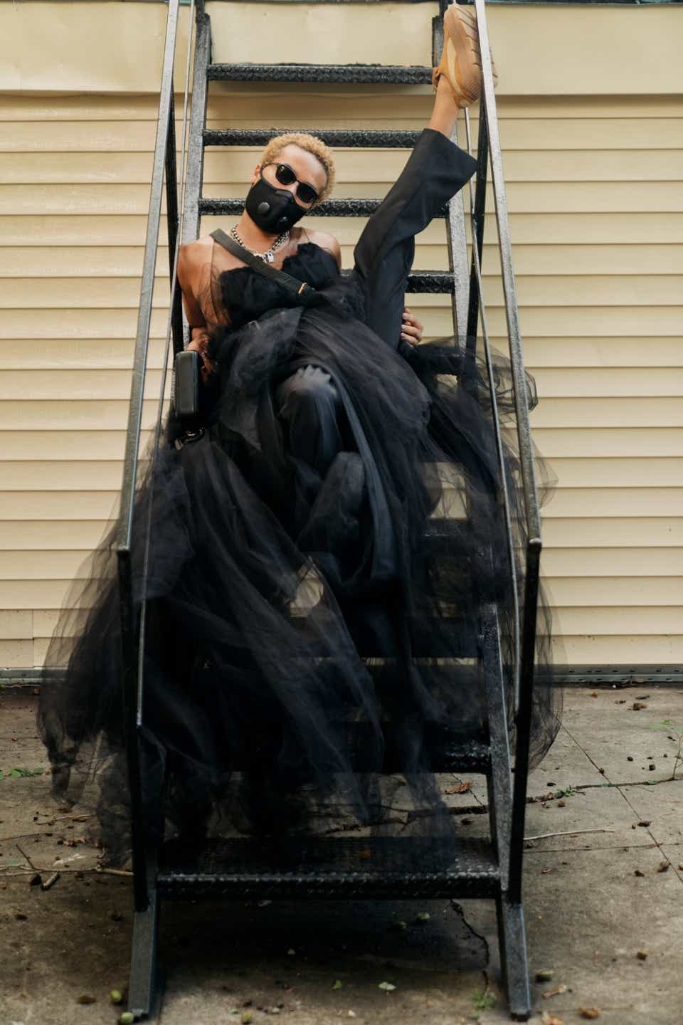 Owen is wearing a black mask and black sunglasses while posing with a leg up on a staircase. Owen is wearing a black, tulle dress with black tuxedo pants.
