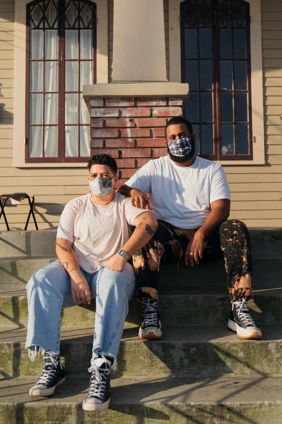 Danny sits on the stoop of her house with a friend. Danny is wearing a tie-dye mask with a plain T-shirt, vintage, light wash jeans, and converse. Her friend is wearing a T-shirt with bleach tie-dyed jeans and JW Anderson x Converse platform high-tops.