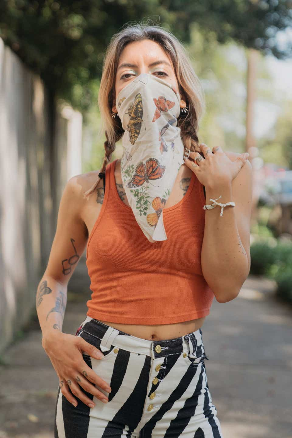 Alynda is wearing a butterfly-covered bandana as a mask with an orange tank top and zebra-print pants.