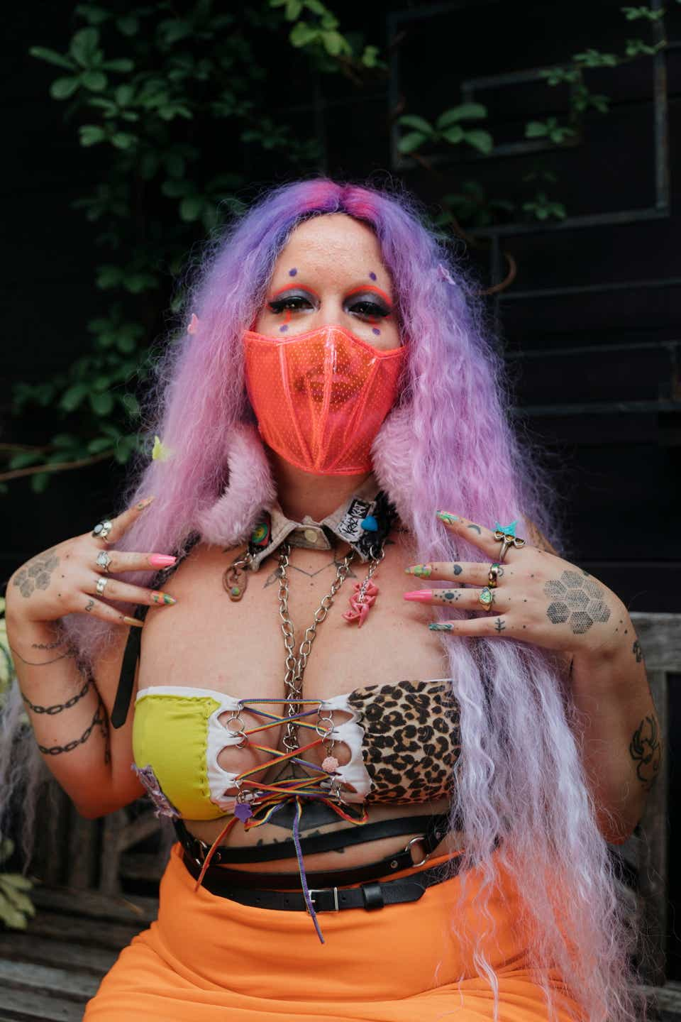 Moody has ombre pink and purple crimped hair. She's wearing a hot pink face mask, a cheetah print tube top, and an orange skirt.