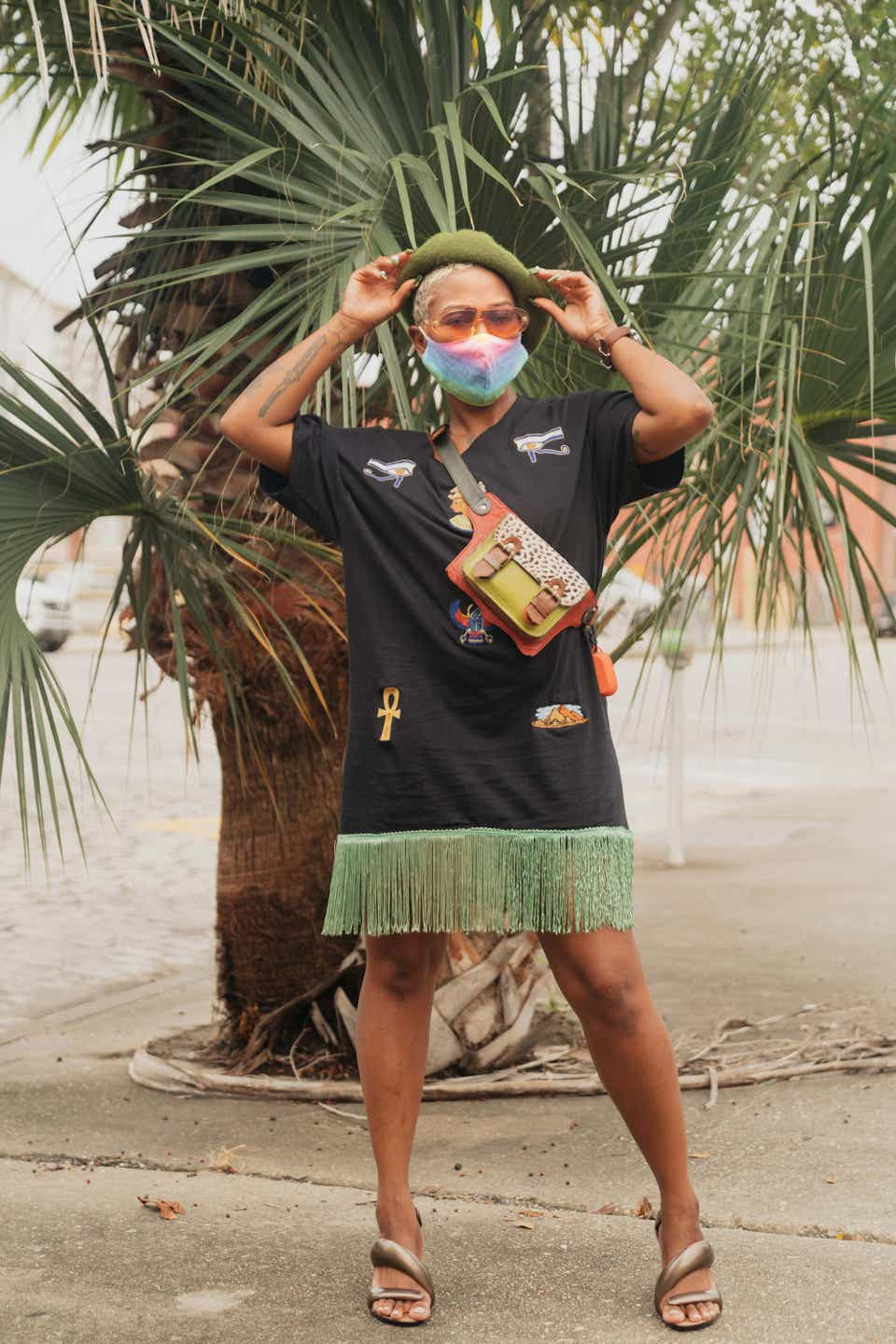 Destine is wearing an army green beret with orange tinted sunglasses and a rainbow tie-dye mask. She has on a black T-shirt dress with green fringe on the bottom. Her shoes are metallic and artfully shaped sandals.