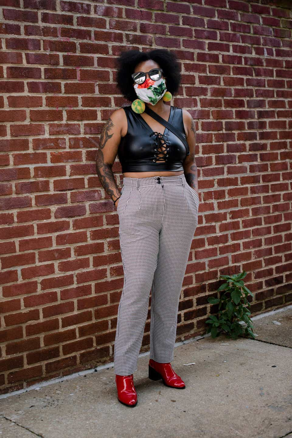 Adesola is wearing a face mask with leaves printed on it and oversized green-and-yellow earrings. She also has on a leather crop top with gray, plaid trousers and red boots.
