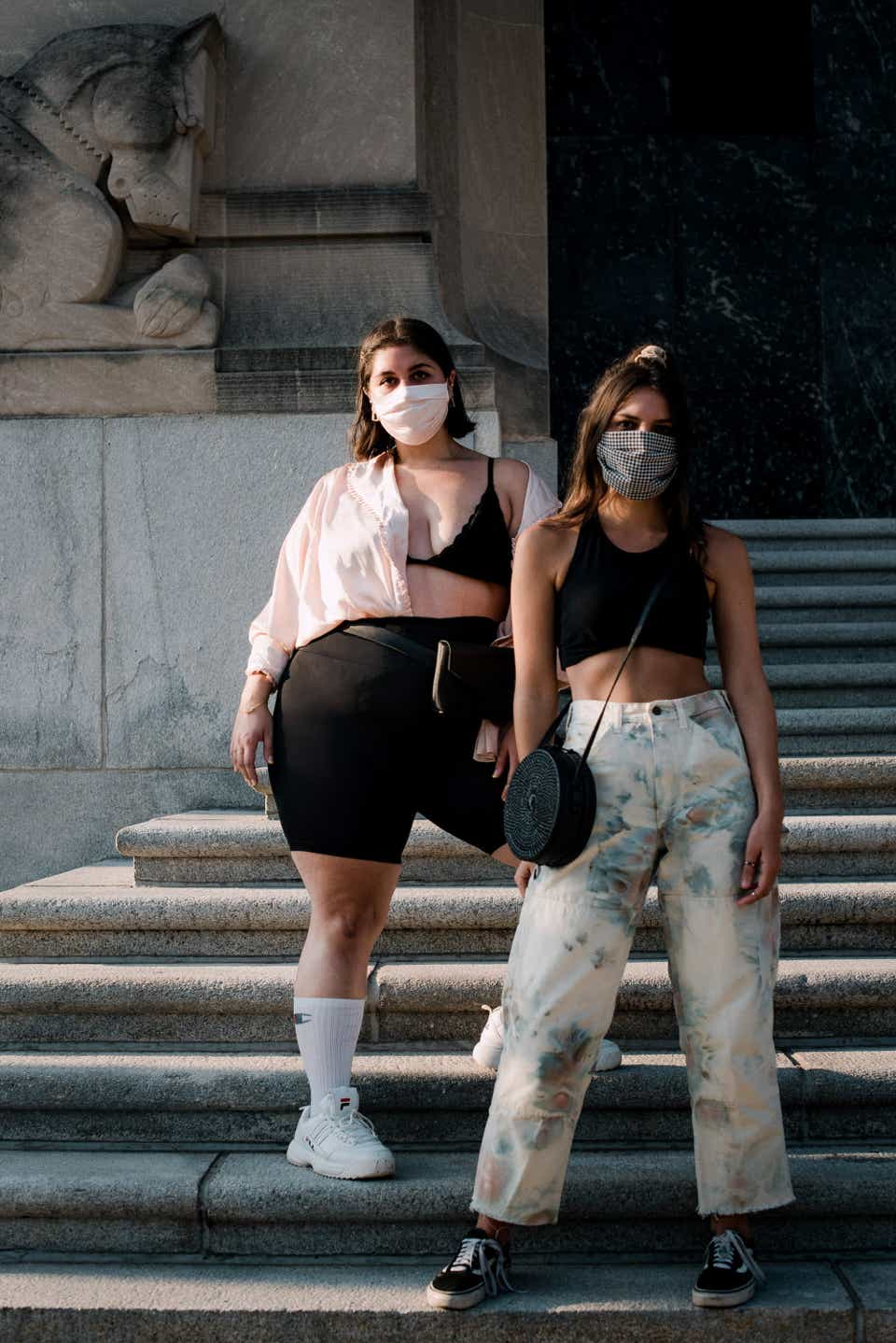 Alesandra and Sam are posing together on a set of historic steps in Philadelphia. Alesandra is on the left and is wearing a light pink blouse that's unbuttoned with a black bralette underneath. With that, she has on black bike shorts, a black fanny pack, tube socks, and FILA sneakers. Sam is wearing a gray mask, a black bralette, and tie-dye carpenter pants. For shoes, she is wearing Vans sneakers.