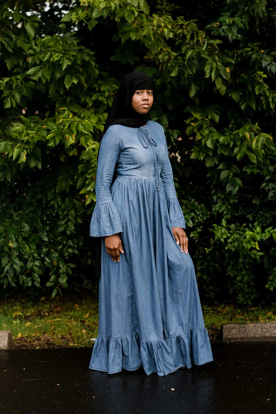 Brittany is wearing a black niqab with a blue chambray maxi dress with bell sleeves.