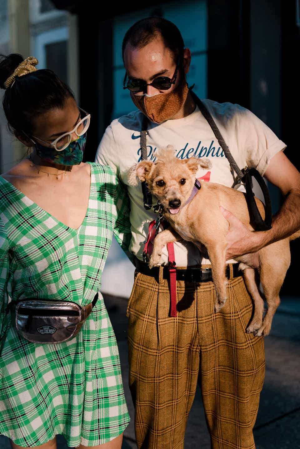 Cindy and Nick are posing together with their dog. Cindy is wearing her hair up in a top-knot with a yellow scrunchie and eyeglasses. She has on a green, plaid dress with a metallic fanny pack. Nick is wearing a terracotta-colored face mask and matching trousers with a vintage NBA T-shirt and suspenders.