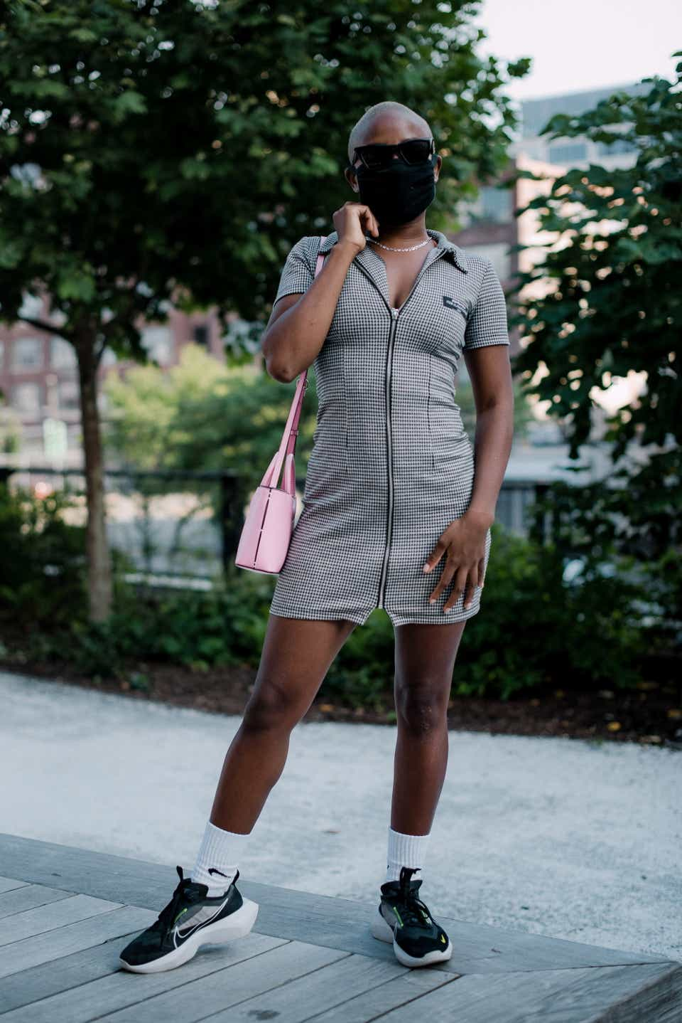 Debora is posing in a park wearing a black face mask and black sunglasses. She has on a black-and-white polo mini dress with a pink handbag, sporty socks, and Nike sneakers.