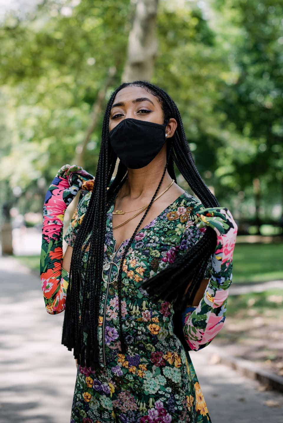 This is a close-up photo of Kassie showing off her braids and her floral elbow length gloves. She's also wearing a black face mask and a floral V-neck jumpsuit.