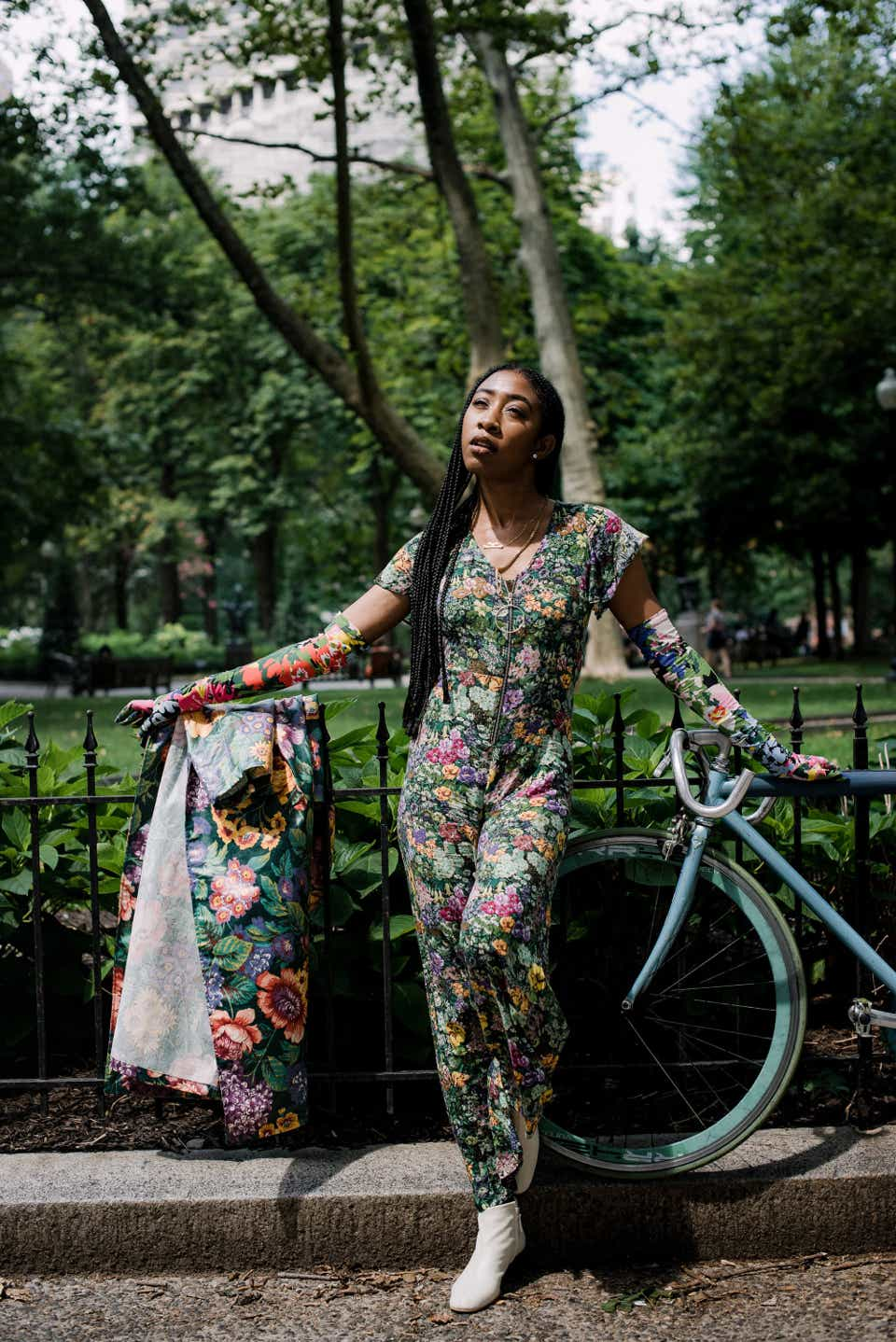 Kassie is posing next to her light blue bike in a park while wearing a floral jumpsuit, floral elbow-length gloves, and a floral jacket.