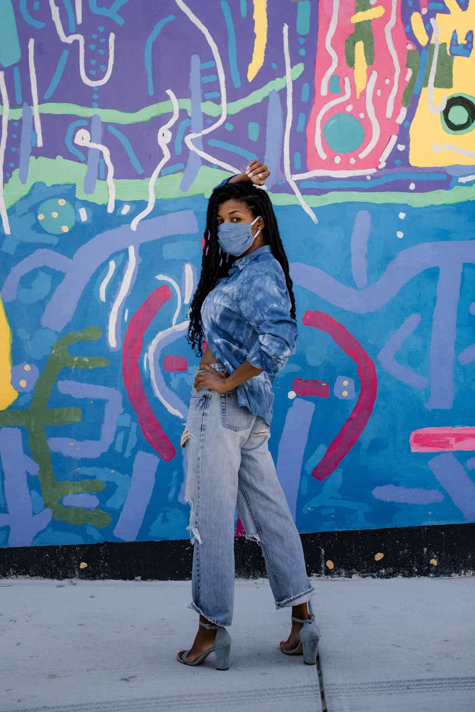 Kimberly is posing against a blue wall with graffiti on it. She's wearing a denim chambray mask with a tie-dye button-down shirt and distressed jeans.