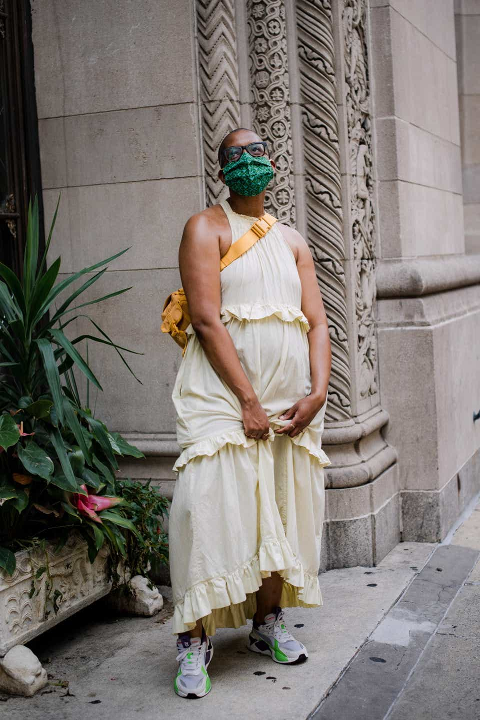 Kristle is wearing a green face mask with a cream-colored, sleeveless prairie dress. She paired the dress with a mustard-colored cross-body bag and sneakers.