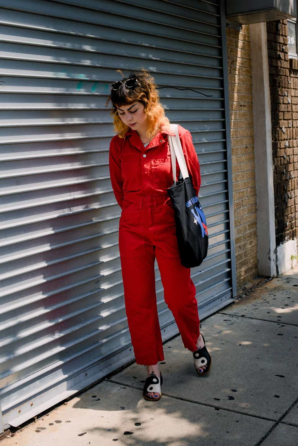 Mia is walking while wearing a red jumpsuit and carrying a black tote bag. Her shoes are ying-yang sandals and she has sandals on her head.