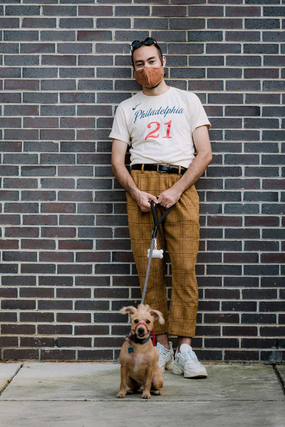 Nick is posing with his dog in a terracotta-colored mask and matching trousers. He also has on a vintage Philadelphia 76ers T-shirt and Adidas sneakers.