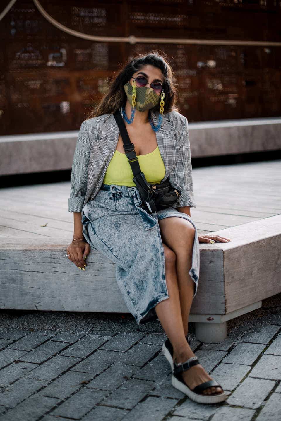 Payal is sitting on a step wearing a mask with a lucite chain attached to it, a gray blazer, a neon green tank top, and an acid-wash knee-length denim skirt. She has on black sandals and a black cross-body bag.