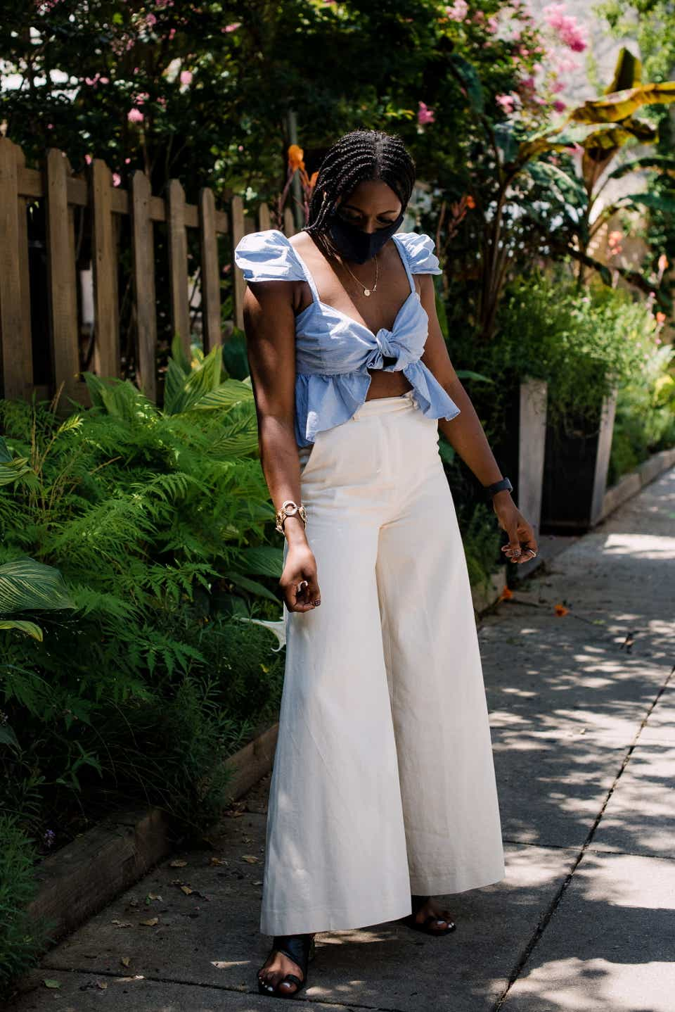 Remul is posing on the sidewalk in a black mask, a light blue, ruffled tank top, and wide-leg white pants.